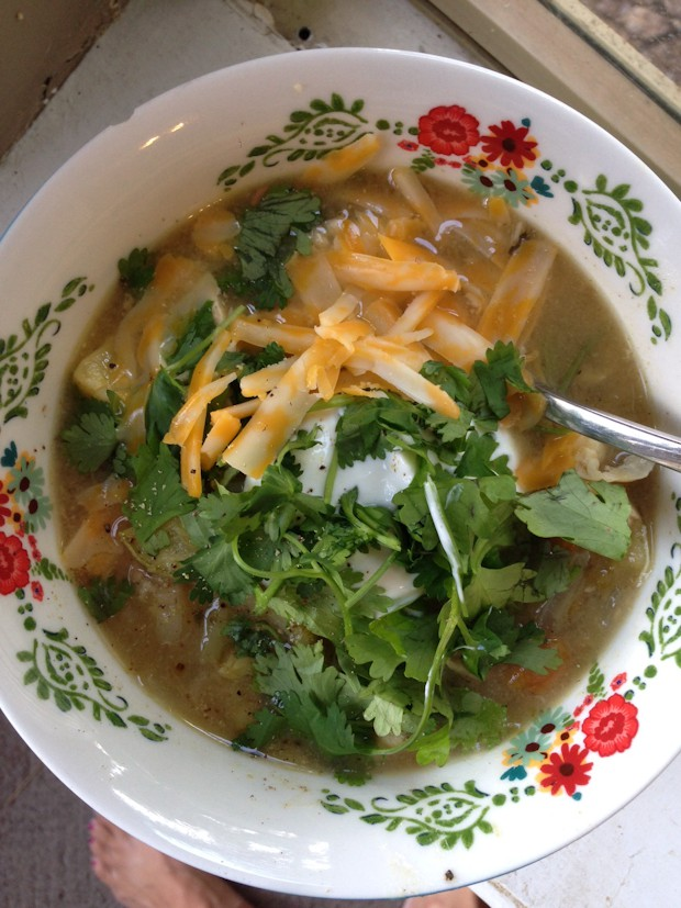 bowl of white chicken chili verde topped with cilantro, shredded cheese, and Greek yogurt with a spoon sitting in the bowl