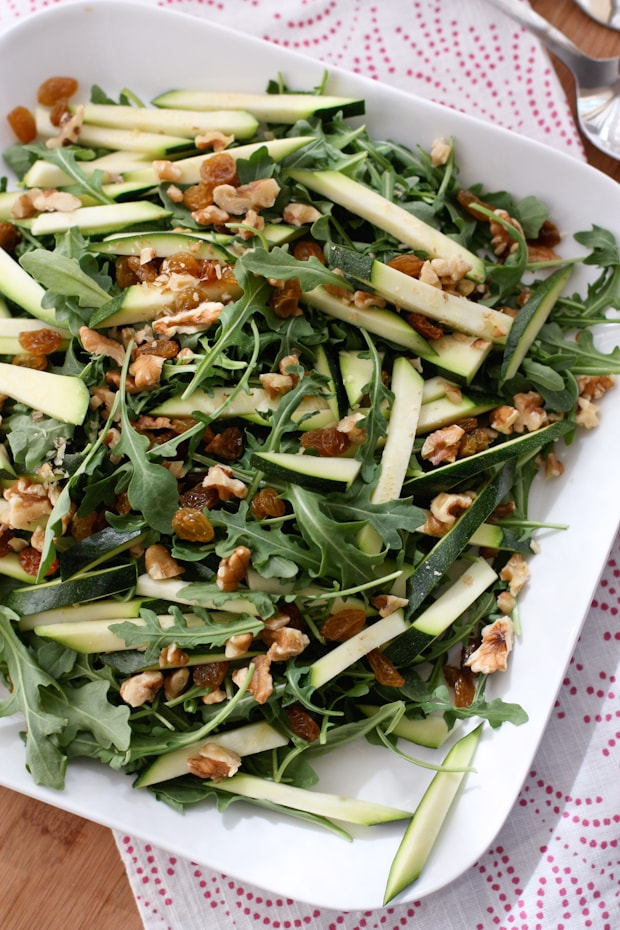 plate of arugula salad topped with walnuts and zucchini strips