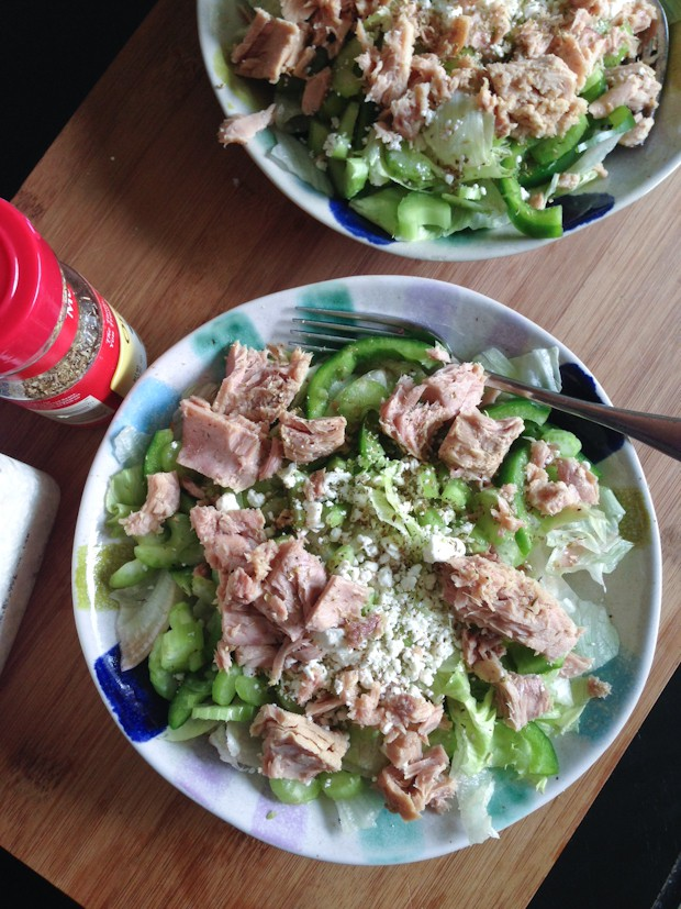 bowl of greens topped with tuna, cucumbers, celery, and peppers sprinkled with cheese