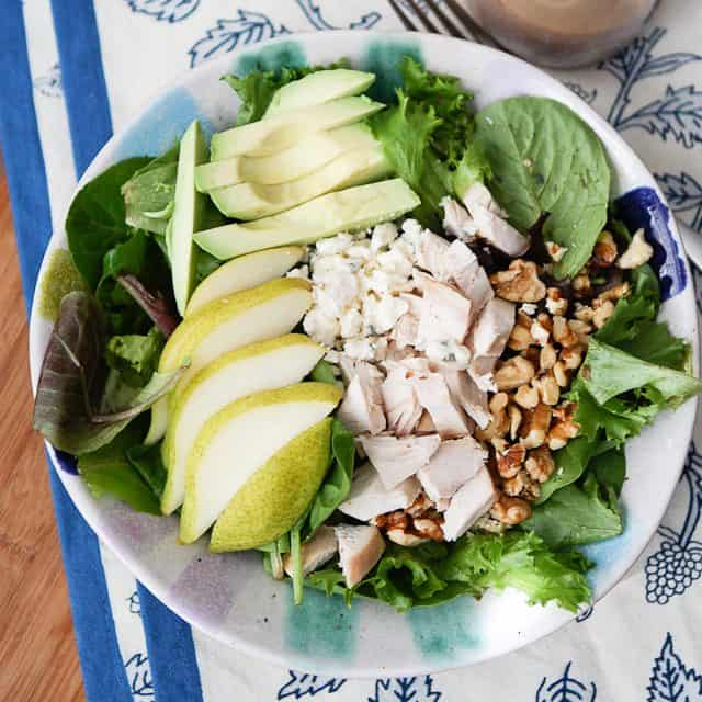 overhead photo of salad plate with greens, sliced pear, sliced avocado, chopped rotisserie chicken and walnuts