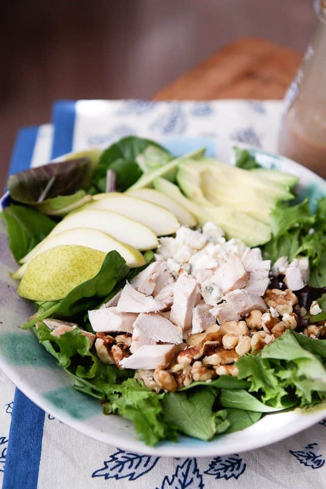 close up of salad with chopped rotisserie chicken, walnuts and sliced pears and avocado