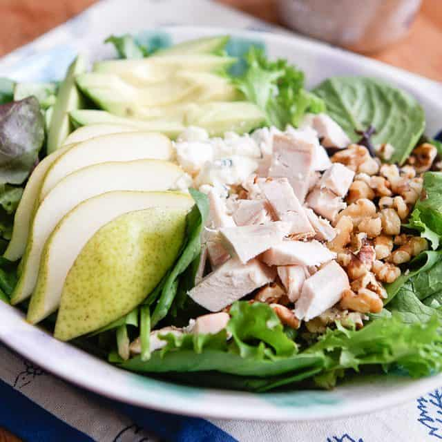 close up of salad with pears, chopped rotisserie chicken, walnuts and avocado