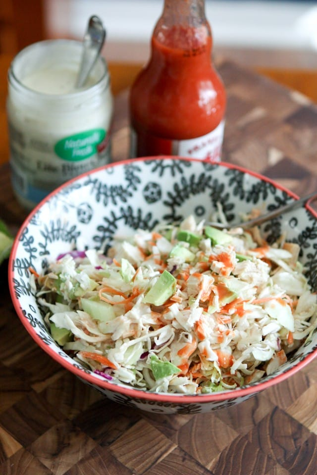 bowl of chicken slaw salad topped with buffalo sauce with containers of blue cheese and buffalo sauce in the background