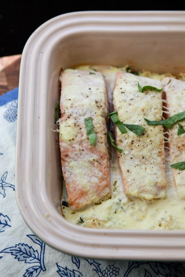 baking container with salmon topped with a creamy sauce and green garnish