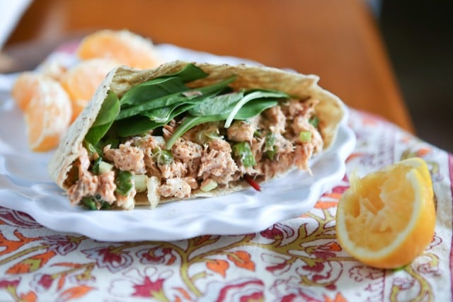 plate of half of a pita stuffed with salmon salad and spinach leaves