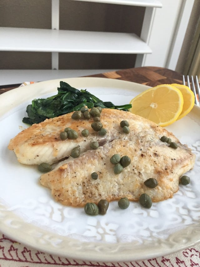 plate of white fish topped with capers with a side of cooked spinach and two lemon slices