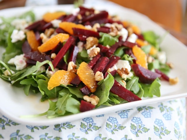 plate of arugula salad topped with goat cheese, beet strips, orange slices, and walnuts