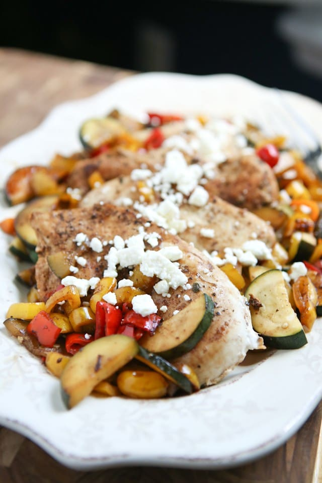 plate of chicken with zucchini, peppers, and corn topped with feta cheese