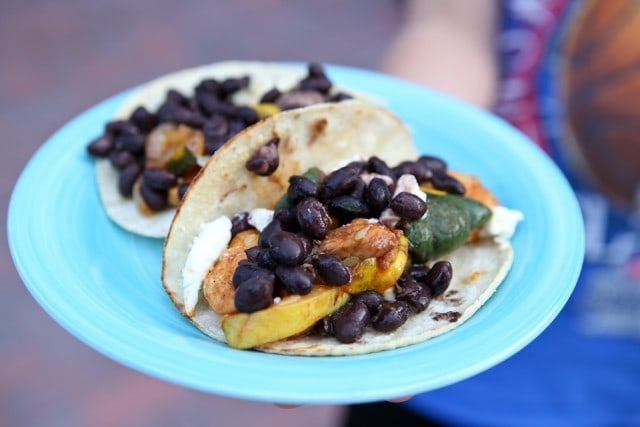 plate of two tortillas with chicken, squash, and topped with black beans