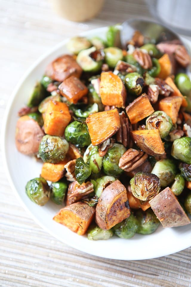 close up of roasted sweet potatoes, brussels sprouts and pecans on a white plate