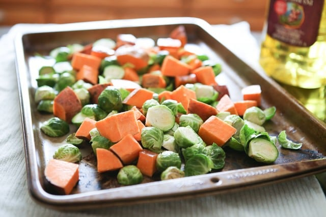 sheet pan with uncooked cubed sweet potatoes and halved brussels sprouts