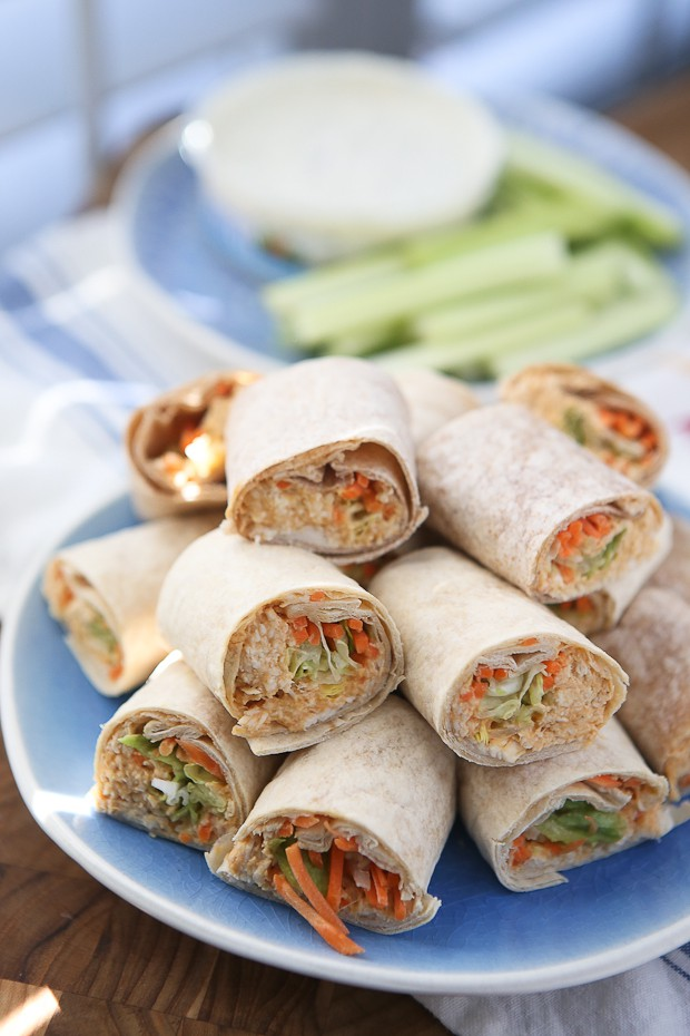 plate of wraps with various vegetables and chicken salad cut in half and stacked on each other