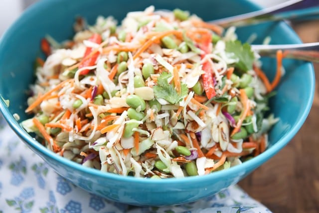 asian slaw salad of slaw mix, mathstick carrots, red bell pepper, Fisher almonds, edamame, and cilantro in a large blue bowl with utensils resting in the bowl