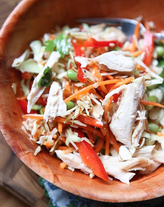 asian slaw salad of slaw mix, mathstick carrots, red bell pepper, Fisher almonds, edamame, and cilantro in a wooden bowl topped with chicken shreds