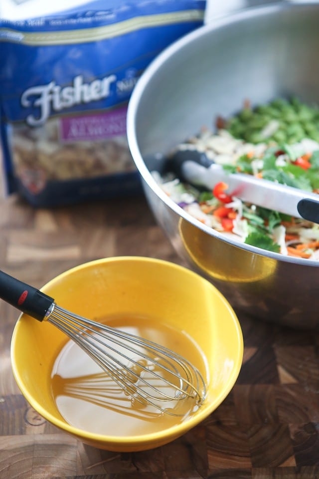 salad dressing being whisked in a small yellow bowl next to the bowl of salad alongside a package of Fisher almond slices