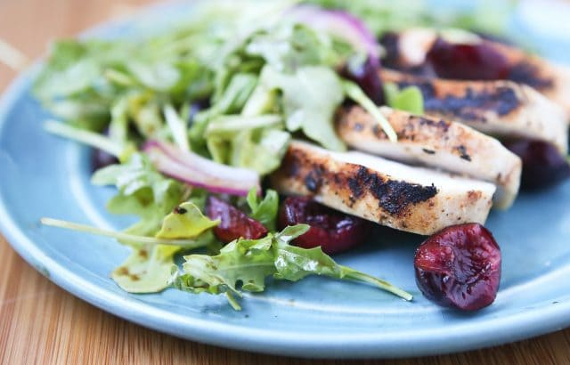 plate with grilled chicken, cherries, and red onions on a bed of arugula