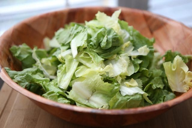 large wooden bowl full of chopped romaine lettuce