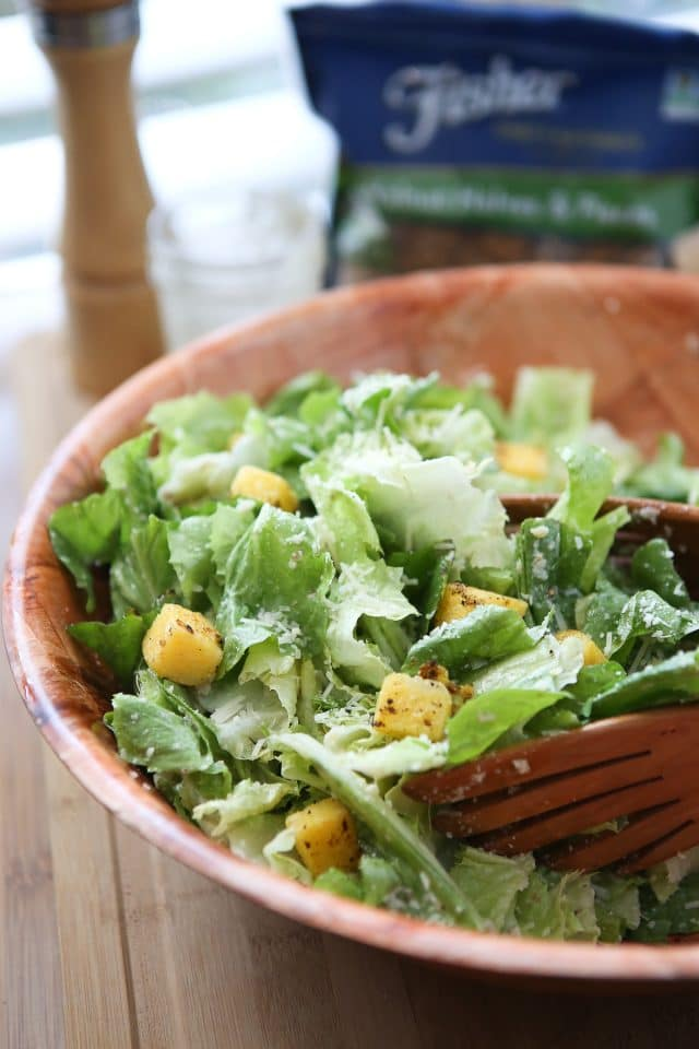 large wooden bowl of caesar salad topped with polenta croutons and parmesan walnut lemon vinaigrette