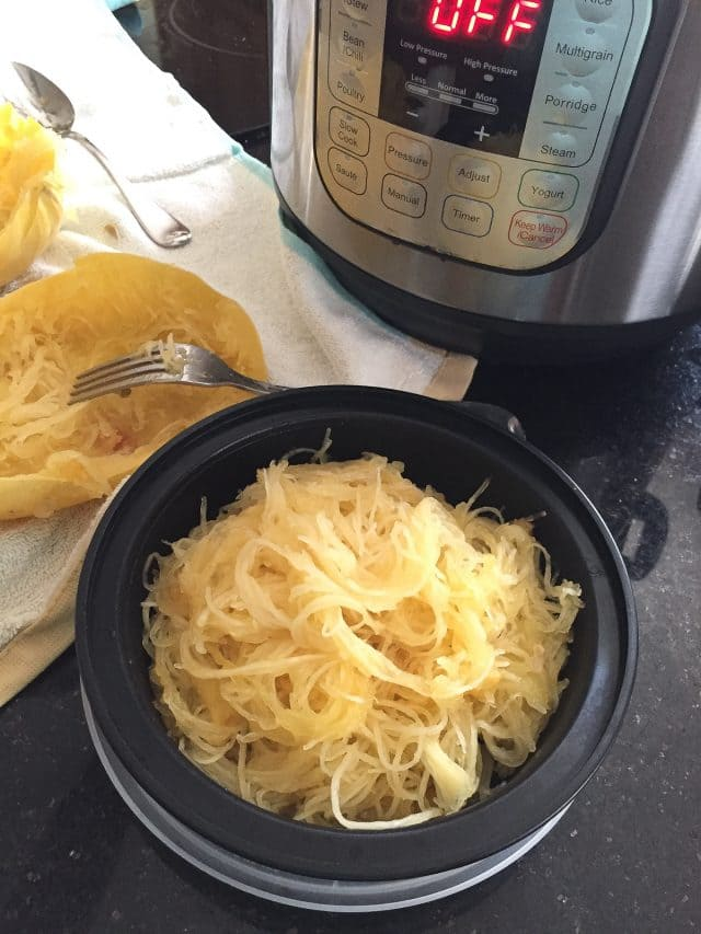 meal prep bowl filled with cooked spaghetti squash with instant pot on counter