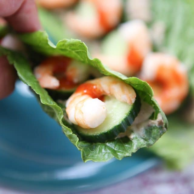 close up of romaine lettuce stuffed with shrimp and cucumber, drizzled with hot sauce