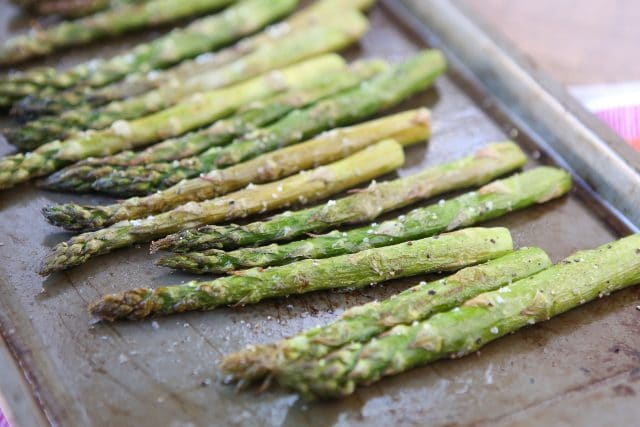roasted asparagus on a sheet pan sprinkled with salt and pepper