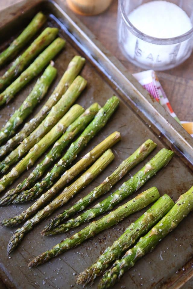 roasted asparagus on a sheet pan with salt and pepper