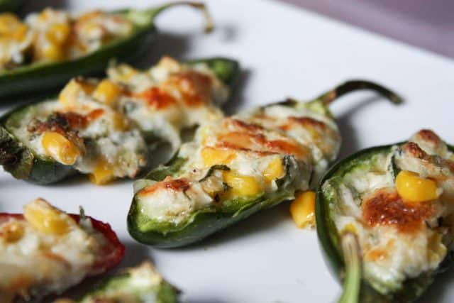 cheese and corn filled jalapenos on white plate