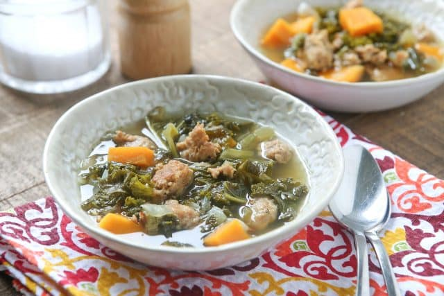 bowl of Italian sausage and kale soup on a colorful napkin with spoon