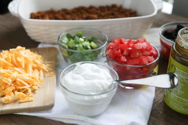 This Layered Taco Dip is full of all the ingredients that we love in our tacos, but in dip form. Great to serve while entertaining family and friends! #UndeniablyDairy #DairyGood #ad