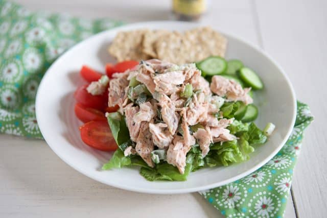 white plate filled with tomatoes, cucumbers and lettuce topped with salmon salad