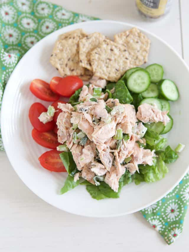 white plate filled with lettuce, tomato and cucumber topped with salmon salad and crackers on side