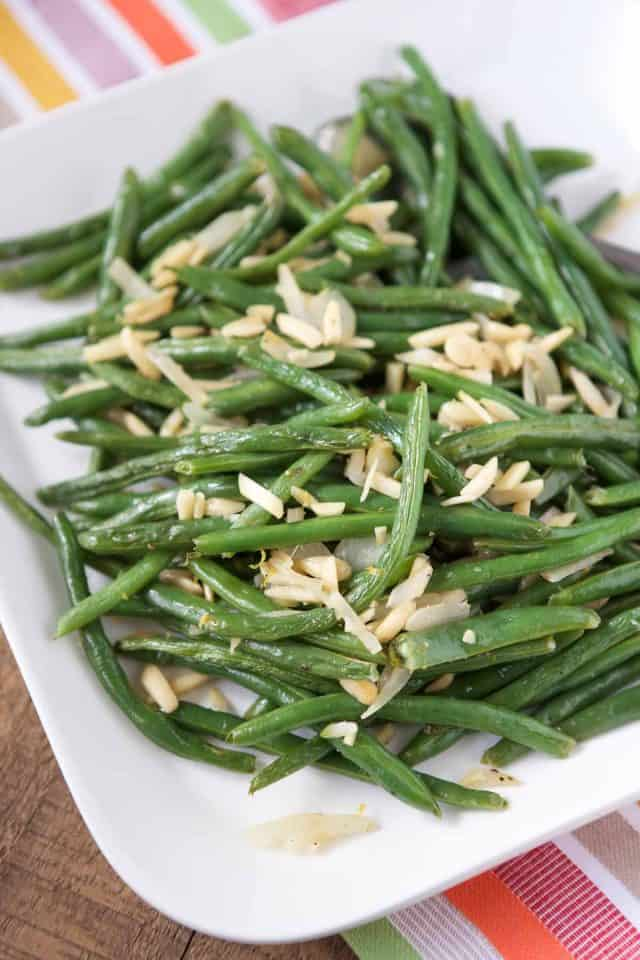 white platter with roasted green beans and almonds