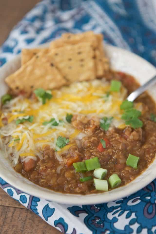 cream colored bowl filled with vegetarian chili topped with melted cheese, green onion, cilantro and crackers